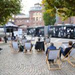 Auftaktveranstaltung aus dem Hintergrund fotografiert. Zu sehen sind Menschen, die in Liegestühlen sitzen und einer Rede zuhören. Die Rednerin steht vor dem Streitbus, der vor der Frankfurter Paulskirche steht.